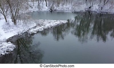 Flight along the riverbank and forest covered with snow on...