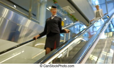 flight attendant and passengers with suitcases down escalator