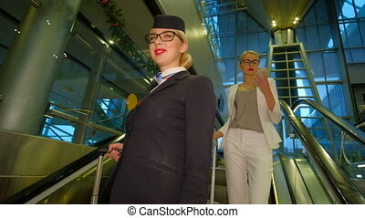 Flight attendant with glasses goes down the escalator and smiling.