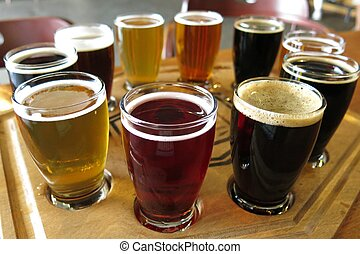 several glasses of various varieties of beer on a wooden tray at a beer tasting