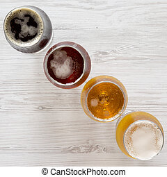 Flight of beers on a white wooden table, top view. Overhead, from above.