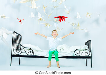 flight of fancy - Cute little boy sitting on his bed...