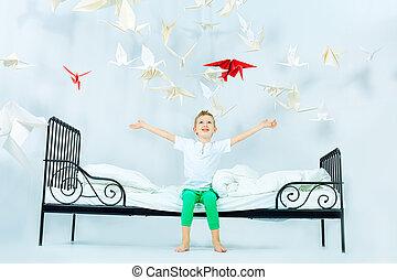 flight of fancy - Cute little boy sitting on his bed ...