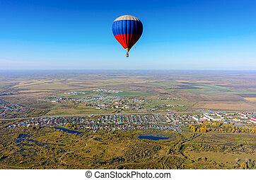 Flight of hot air balloon over rural landscape