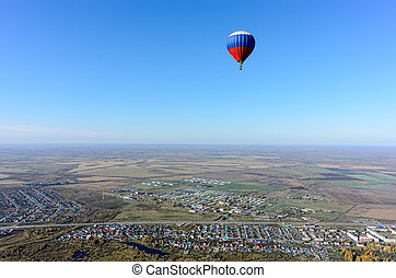 Flight of hot air balloon over rural landscape
