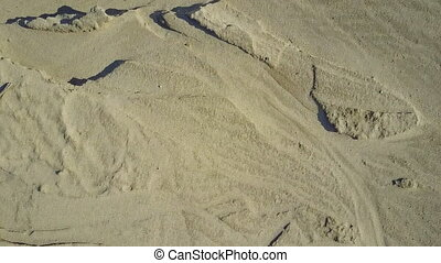Flight on quadcopter over sand. Top view