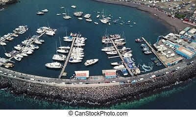 Flight over a dock with a lot of yachts and boats on the...