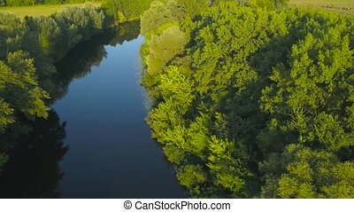 Flight over a quiet river surrounded by green trees at...