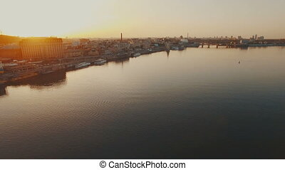Flight over a river port in a European city at sunset aerial