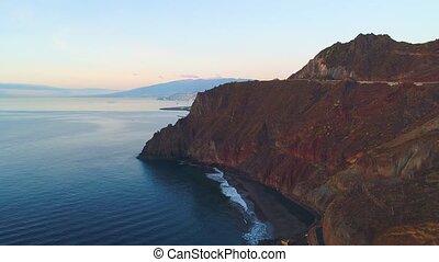 Flight over a seashore at sunrise near Teresitas beach in...