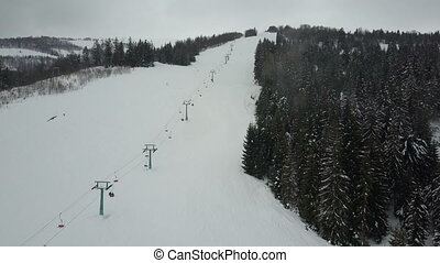 Flight over a ski lift in Carpathian mountains. Aerial view of people descending on skis.