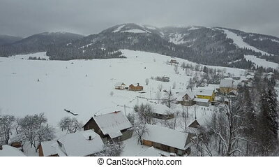 Flight over a village in Carpathian mountains. Bird's eye view of snow-covered houses in mountains. Rural landscape in winter. Carpathian village in the snow from a height.