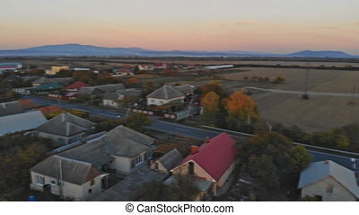 Flight over a village in fall. Beautiful arial view to with small houses in autumn.