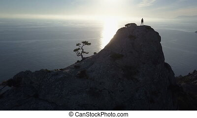 Flight over a young woman standing on the top of a mountain facing the sea. Lady on the summit in beautiful scenery.
