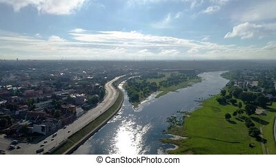 flight over city on river bank - flight over green city on...