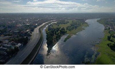 flight over city on river bank - flight over green city on...