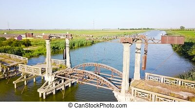 Aerial shot of an old and broken bridge over the river with birds flying