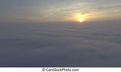 Flight over field of clouds in sunrise time