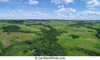 flight over green meadows and blue sky land - aerial view of...