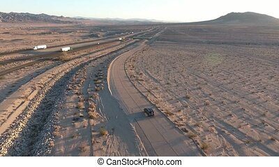 Flight over long highway at monument valley in Utah - Drone Aerial over cars in Arizona. Top view drone footage flying over dry and beige desert, drought resulted landscape, global warming threat
