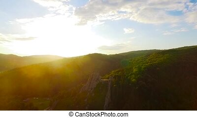 Flight over mountains with forests, meadows and hills in sammer sunset soft light. Carpathian Mountains, Ukraine