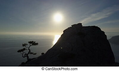 Flight over of young woman standing on the top of a mountain facing the sea. Lady on the summit in beautiful scenery.
