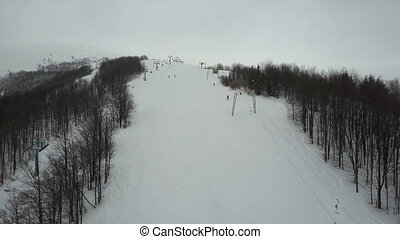 Flight over people using ski lift in mountains. Aerial view of ski resort.
