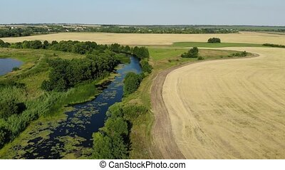 Flight over plain with river and pond in July in Russia -...