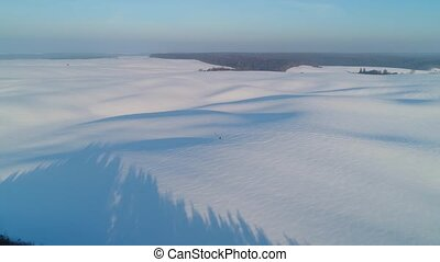 Flight over snow-covered fields. Long shadows of hills. Man travels alone.