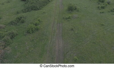 Flight over the country road with the camera rising to the...