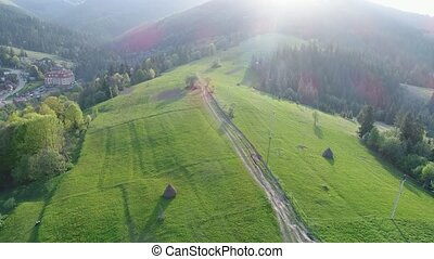 Flight over the forest in the mountains and village . Aerial...