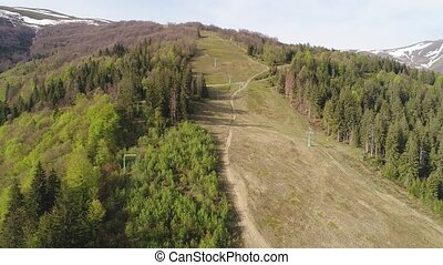 Flight over the forest with lifts in the mountains. Aerial...