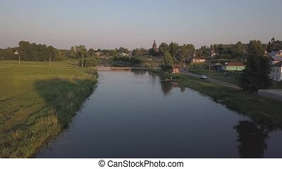 Flight over the river Kamenka in the ancient Russian city of Suzdal at sunset.