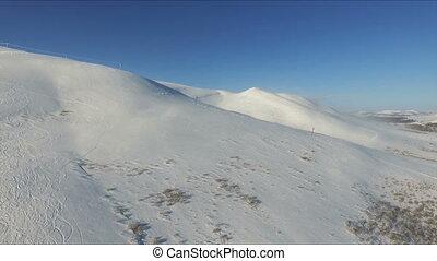 Flight over the slope in mountain ski resort.