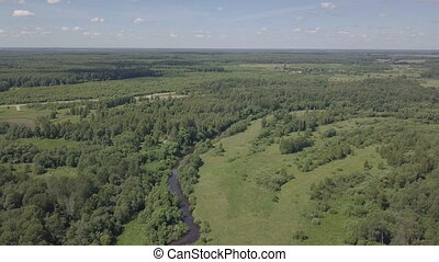 Flight up over river. Aerial landscape. Small river, trees...