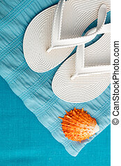 280447228 Flip flop near seashell on blue background. Top view.