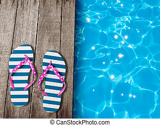 flip flop sandals on old wooden boards near swimming pool