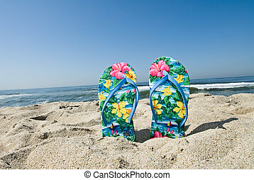 Flip flops - A pair of flip flops stuck in the sand by a...