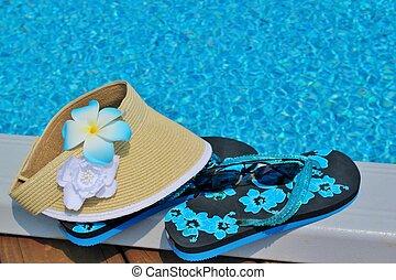 Flip flops and a sun visor on the edge of a pool