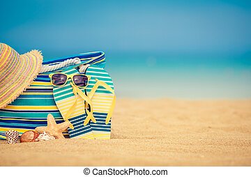 Summer vacation concept - Flip-flops and bag on sandy beach ...