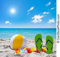 flip flops and beach ball under a shining sun