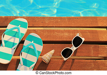 Flip flops and sunglasses on wooden planks and water