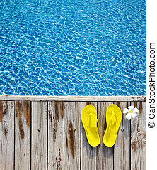 Flip-flops by a swimming pool - Yellow flip-flops by a ...