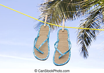 A pair of flip flops drying in a tropical breeze on a clothesline.