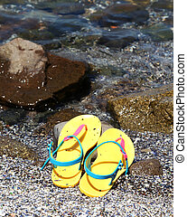 flip flops in the water line at a beach