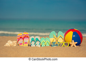 Summer vacation concept - Flip-flops on sandy beach against...