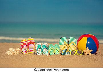 Summer vacation concept - Flip-flops on sandy beach against...