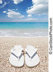 Flip flops on the beach - White flip flops on sea beach
