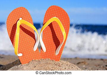 Orange flip-flops in sand on the beach in Barcelona.