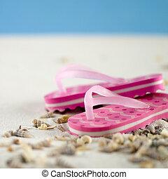Flip Flops - pair of pink flip flops in the sand